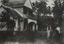 Obchod Ben Varnayho, kde Gauguin nakupoval. Muž na koni je majitel a uzdu drží Gauguinův přítel a soused tesař Tioka.